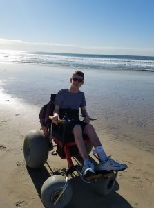 Daman rides a beach wheelchair at the beach