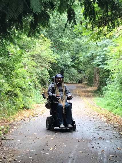 Ian, a man with long dreads sitting in a power wheelchair, riding on a leaf-covered, paved bike trail near Sequim, Washington.