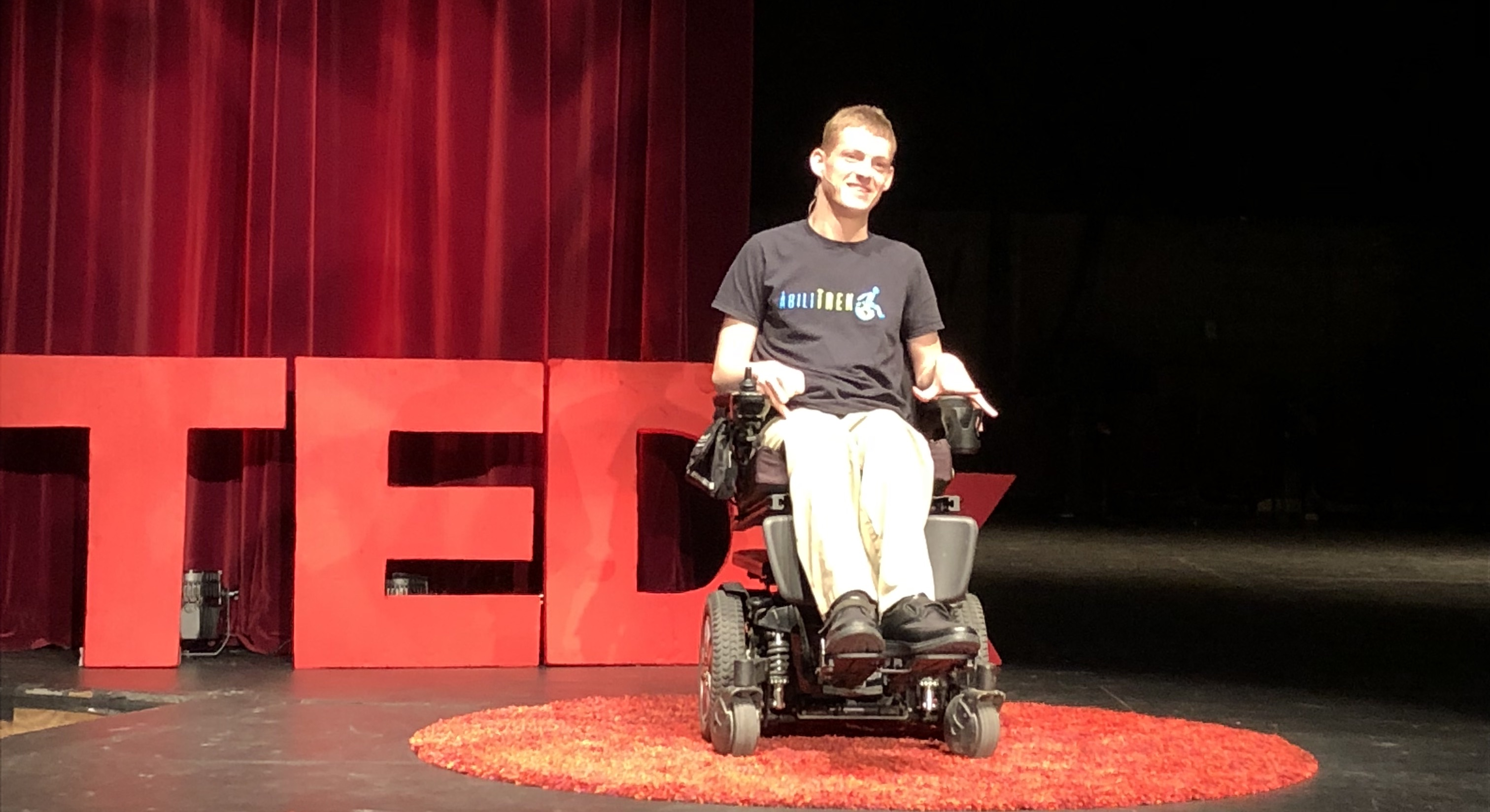 Daman sitting in his power wheelchair on the stage speaking at the 2018 TEDxWWU. There is a red TEDx behind him a red curtain behind the TEDx. He is wearing an AbiliTrek t-shirt (black shirt with neon blue and lime green lettering),  tan slacks, black shoes and a head-set mic.