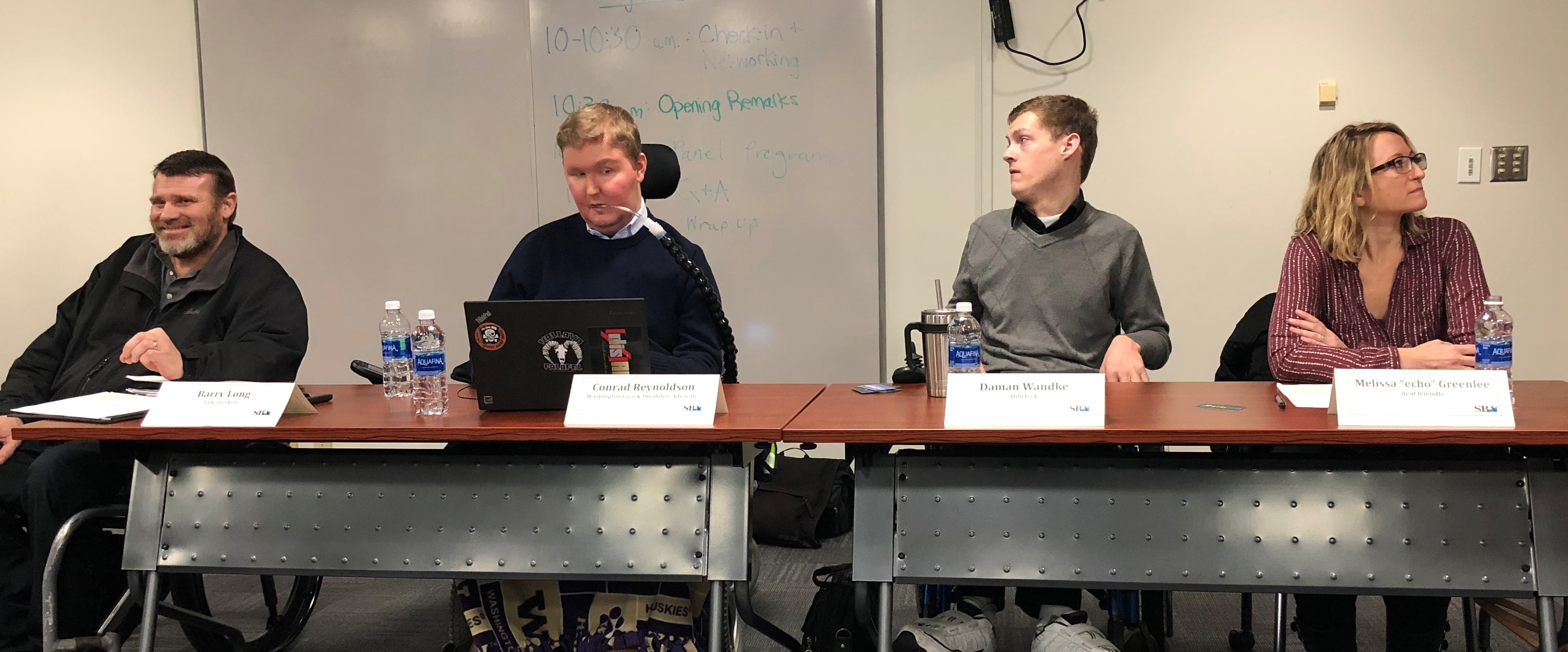 Daman sitting on a disability lead panel. He is the third from the left. Daman is wearing a grey sweater with a black collar. Barry, the first man on the left, is wearing a black, zip-up jacket, and is speaking. Conrad is second from the left; he is wearing a dark blue sweater with a white collar and is looking at his laptop. Melissa is sitting the fourth from the left.