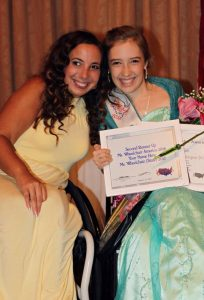 Kyann, with Ms. Wheelchair America board member, Stephanie, at the Ms. Wheelchair America 2018 Crowning Night. Both ladies are smiling. Stephanie is wearing a yellow, high-necked, sleeveless formal dress. Kyann is wearing a strapless, turquoise, formal dress. She is wearing her Ms. Wheelchair Washington sash as well as holding her Second Runner-Up and Emerging Leader Award plaques.