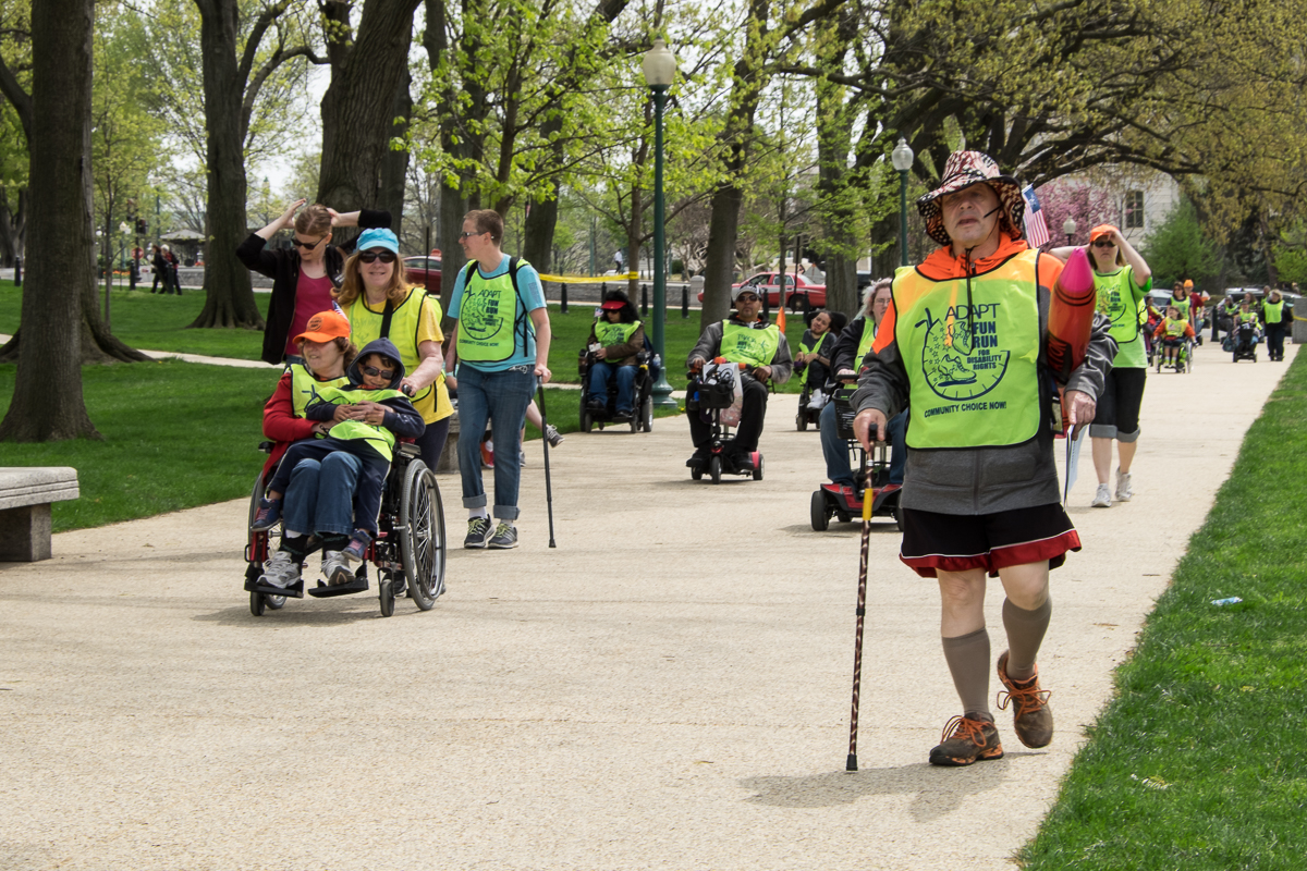 A large group of people, all of whom have varying disabilities, moving towards the camera, together.