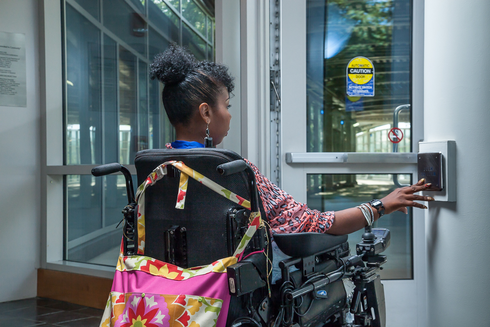 A woman in a power wheelchair, pressing the access button in order to open the door in which she is facing.