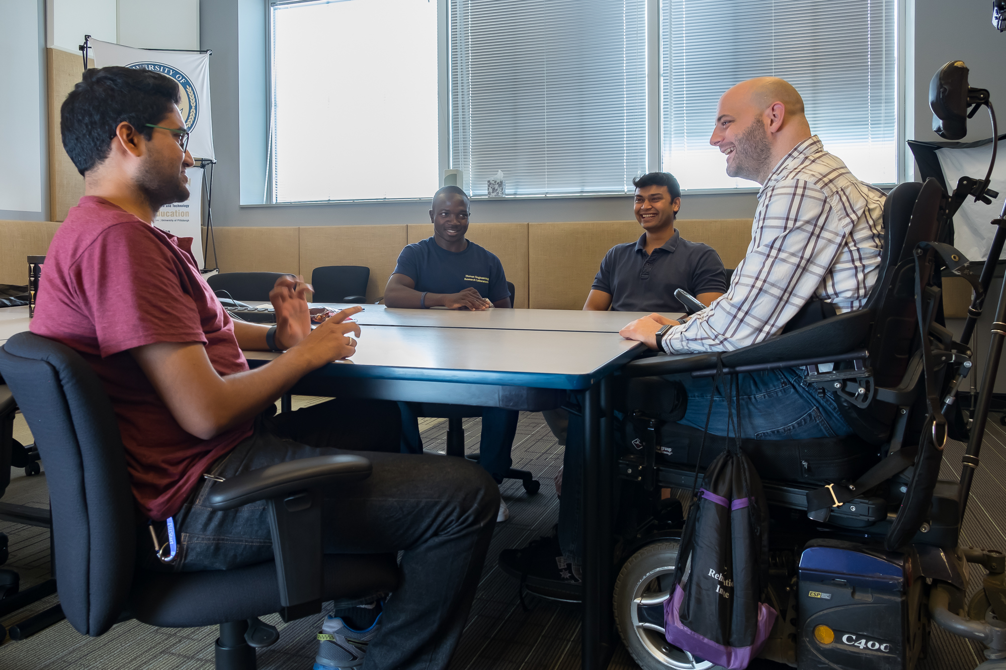 Four people sitting around a conference table, three in black office chairs and one in a power wheelchair.