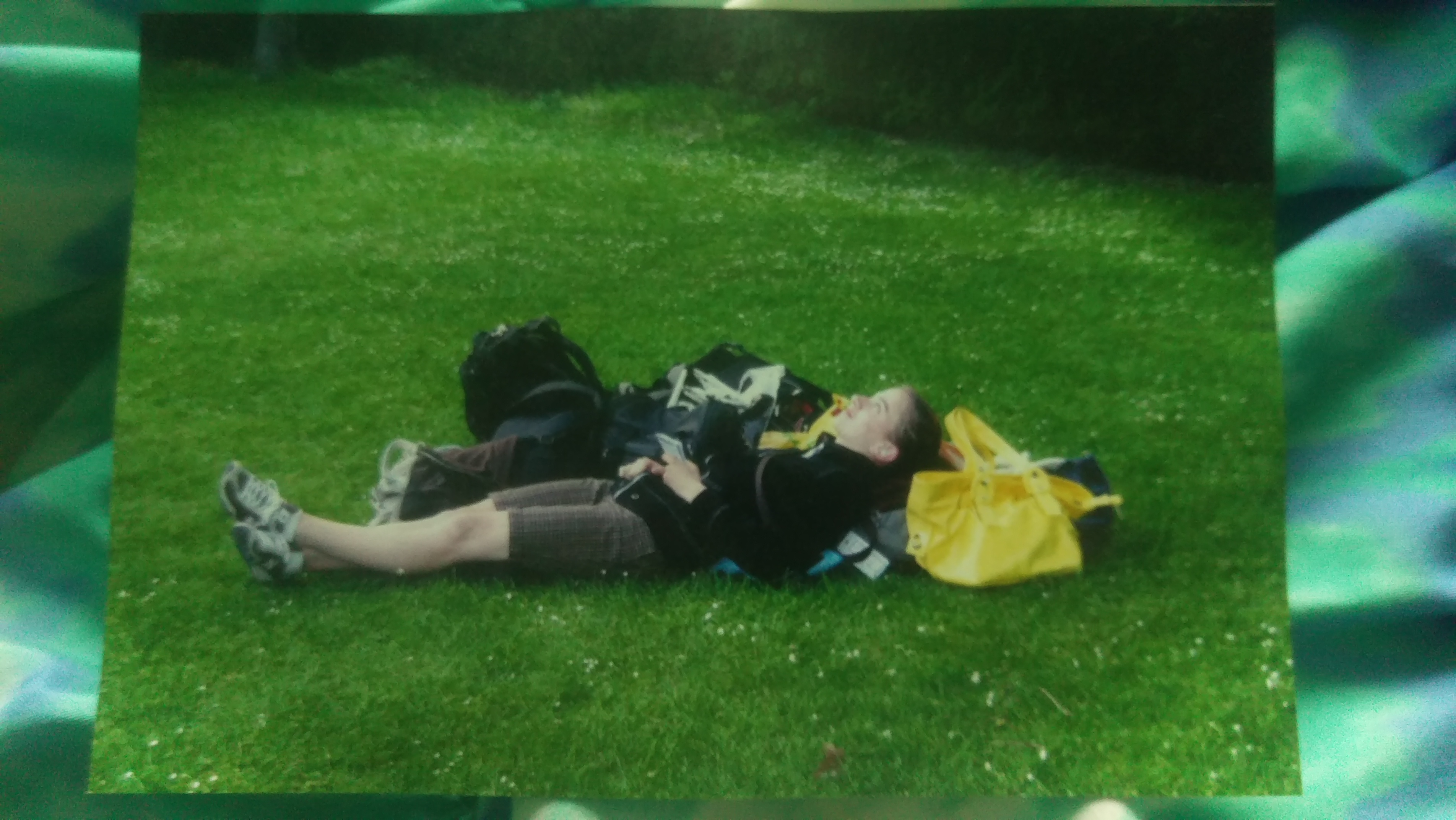 A picture of a picture of Cora laying in  a field of grass with her day pack and travel pack.