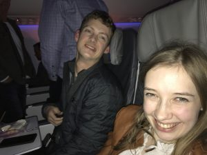 Daman and Kyann sitting in their seats on a plane, Daman on the left, Kyann on the right. They are both smiling.