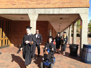 Daman with five others all moving toward the camera. Daman and three others are in their cap and gown, the fifth person is in a suit.