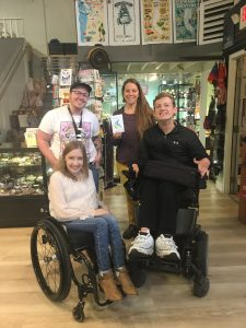 Kyann, Daman, Oliver and Erika in a photo together. Kyann is sitting in her manual wheelchair in the front left of the photo and Oliver is standing behind Kyann. Daman is sitting in his power wheelchair to the right of Kyann, in the front right. Erika is standing behind Daman and is holding the ACP decal. They are all smiling.