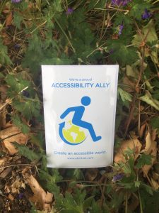 """A photo of the ACP decal with green leaves behind it. The ACP decal is a vertical, rectangular window decal. At the top in light blue lettering reads, """"We're a proud disability ally."""" The """"We're a proud"""" is written out in typical fashion while """"disability ally"""" is written out in capital letters. Under that is the AbiliTrek logo, the light blue, wheelchair, stick-figure symbol with a lime green word for a wheel. Under the AbiliTrek logo reads, """"Create an accessible word,"""" in light blue lettering. Under that, www.abilitrek.com i spelled out in light blue as well."""